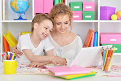 Mom and son doing lessons. At the table Royalty Free Stock Photography