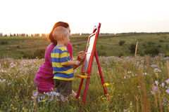 Mom with son draw on nature. A Mom with son draw on nature , beautiful sunset Royalty Free Stock Photography
