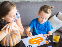 Mom with son draw a pumpkin for Halloween Royalty Free Stock Images