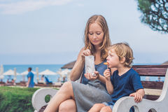 Mom and son eat fried sweet potatoes in the park. Junk food conc Royalty Free Stock Photos