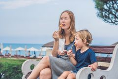 Mom and son eat fried sweet potatoes in the park. Junk food conc Stock Photography