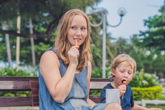 Mom and son eat fried sweet potatoes in the park. Junk food concept Royalty Free Stock Images
