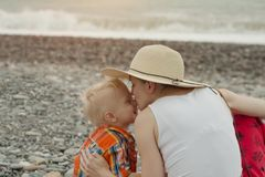 Mom and son embrace on a pebble beach. Sunset time. Back view stock image