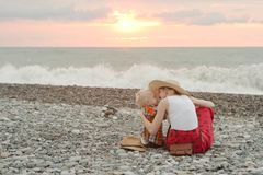 Mom and son embrace on a pebble beach. Sunset time. Back view stock photography