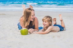 Mom and son enjoy the beach and drink coconut royalty free stock photography