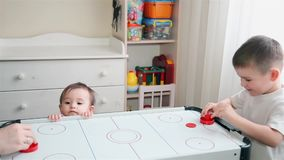 Brother plays air hockey and little sister watches him HD 1920x1080 stock video