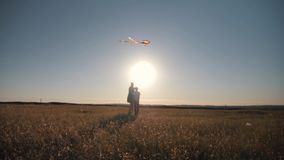 Mom and son fly a kite in a field at sunset.