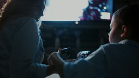 Mom with son in front of the TV playing video games and pass each other the joystick. Rear view of the TV screen. Mom with son in front of the TV playing video stock footage