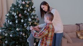 Mom and son hanging grey knitted socks for presents on Christmas tree at home. stock footage