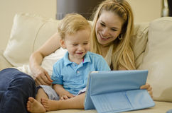 Mom and son having fun. Cute young mother and her son having fun with a tablet computer Royalty Free Stock Image