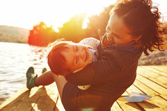 Mom and son having fun by the lake. Warm filter and film effect Royalty Free Stock Photos