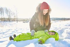Mom and son having fun. Young beautiful Caucasian women playing with her little boy lying on snow and smiling at camera happily on bright winter afternoon Stock Photos