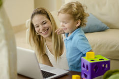Mom and son having fun. Young mother and her son laughing and having fun with a computer Royalty Free Stock Image