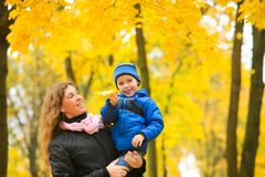 Mom with son in her arms walks in  autumn park