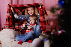 Mom and son hid under a blanket. Waiting for the Santa Claus. Mom and son playing in the house under a blanket on the background of Christmas tree stock photography