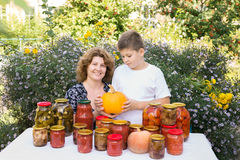 Mom with son and home canned vegetables Stock Image