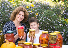 Mom with son and home canned vegetables Royalty Free Stock Image