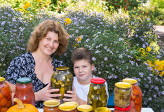 Mom with son and home canned vegetables Stock Photo