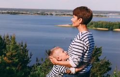 Mom and son are hugging on the background of a big river. Family look royalty free stock image