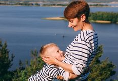Mom and son are hugging background of a big river. Mom and son are hugging on the background of a big river, family look royalty free stock image