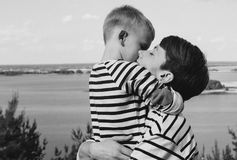 Mom and son are hugging on the background of a big river. Stile life stock photo