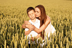 Mom and son are hugging in the summer on a wheat field. Mom and son are hugging in the summer on a yellow wheat field royalty free stock photo