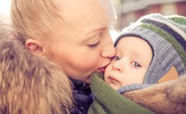 Mom and son. Mom kissing her handsome son - Woman and baby outdoors Stock Image