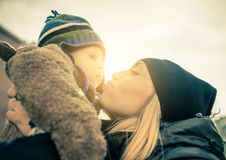 Mom and son. Mom kissing her handsome son - Woman and baby outdoors Stock Photo