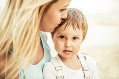 Mom and son. Mom kissing her handsome son - Woman and baby outdoors Royalty Free Stock Images