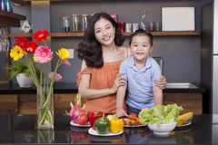 Mom and son in the kitchen with a lot of fruit and vegetable. Mom and son in the kitchen with a lot of fruits and vegetables Stock Photo