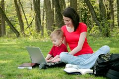 Mom and son on laptop. A mother and her boy child learning on a laptop computer in the park Royalty Free Stock Photos