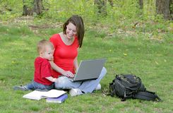 Mom and son on laptop. A mother and her boy child learning on a laptop computer in the park Royalty Free Stock Images