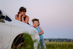 Mom and Son Leaning Against the Car While Waiting Stock Photos