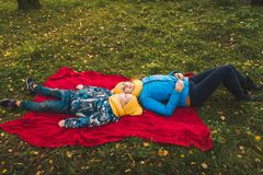 Mom and son lie on a blanket on the grass royalty free stock photography