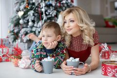 Mom and son lie near the New Year tree with big cups of cappuccino and marshmallows. Beautiful women and her five year old son lie side by side on a white floor stock photo