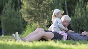 Mom, son and little daughter are playing with a stone scissors paper in the par. K. My daughter is sitting with her mother in her arms. Spring is outdoors. The