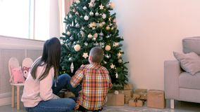 Mom and son look at Christmas toys sitting near Christmas tree at home. stock video footage