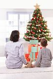 Mom and son looking at christmas tree. Mom and son sitting together, holding hands with toy, looking at christmas tree and presents on christmas morning Royalty Free Stock Photos