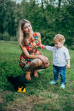 Mom and son are looking at the kittens. Mom and son walk in the park outside the city in the evening Royalty Free Stock Images