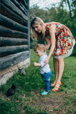 Mom and son are looking at the kittens. Mom and son walk in the park outside the city in the evening Stock Image