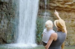 Mom and son are looking at the waterfall, the view from the back Stock Image