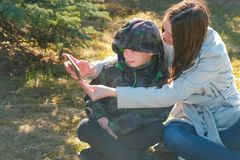Mom and son make selfie on mobile phone in spring park. stock image