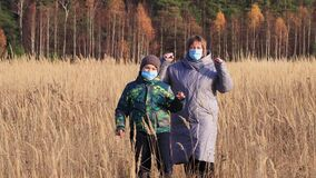 Mom and son in masks are dancing in the tall grass.