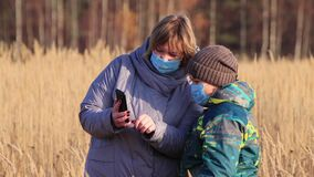 Mom and son in masks, in the tall grass, are looking at photos on the phone.