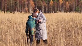 Mom and son with masks on their faces in the field use the phone