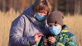 Mom and son with masks on their faces are talking online on a smartphone.