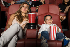 Mom and son on a movie date. Beautiful young women and her son watching a movie in a cinema theater during a date night royalty free stock photography