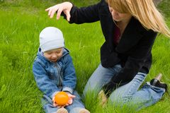 Mom.son.orange. Mom and the son play with an orange on a grass. Spring Royalty Free Stock Photos