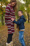 Mom and son in park. Small boy kissing belly of his pregnant mother outdoors royalty free stock image