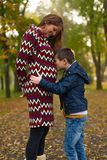 Mom and son in park. Small boy kissing belly of his pregnant mother outdoors stock photo
